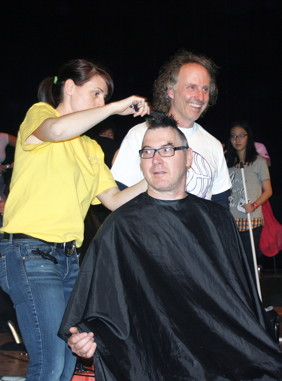 Staff getting hair cut at Cut for the Cure day